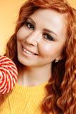 Młoda rozochocona kędzierzawa rudzielec kobieta trzyma dużego słodkiego lizaka zdjęcia stock