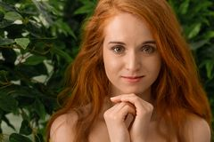 Młoda rudzielec dziewczyna patrzeje kamerę, zieleń opuszcza tło fotografia stock