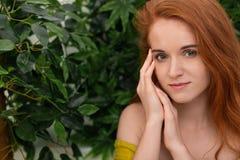 Młoda rudzielec kobieta dotyka jej twarz, zielony tło zdjęcie royalty free
