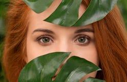 Młoda rudzielec kobieta z naturalnym makeup przy zielonym monstera opuszcza zdjęcia royalty free