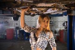 Młoda seksowna mechanik kobieta w rozpinającej pasiastej koszulowej pozycji pod samochodem w samochodowej remontowej usłudze obrazy royalty free