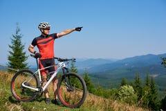 Młoda sportowa fachowa rowerzysta pozycja z bicyklem na górze wzgórza zdjęcie royalty free