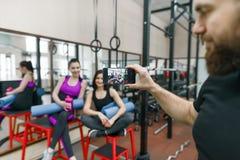 Młoda sportowa uśmiechnięta kobieta śmia się w gym, fotografującym na telefonie komórkowym Sprawność fizyczna, sport, szkolenie,  obraz stock