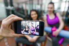 Młoda sportowa uśmiechnięta kobieta śmia się w gym, fotografującym na telefonie komórkowym Sprawność fizyczna, sport, szkolenie,  zdjęcie stock