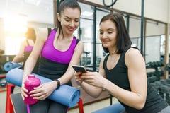 Młoda sportowa uśmiechnięta kobieta w gym z telefonem komórkowym Sprawność fizyczna, sport, szkolenie, ludzie, zdrowy styl życia  zdjęcia stock