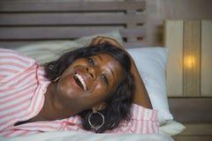 Młoda szczęśliwego, pięknego czarnego afrykanina Amerykańska kobieta w piżam kłamać i figlarnie na łóżkowy ono uśmiecha się rozoc zdjęcie royalty free