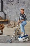 Młoda uśmiechnięta kobiety próżnia czyści dywan w żywym pokoju, nowożytny scandinavian wnętrze Dom, housekeeping fotografia stock