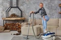 Młoda uśmiechnięta kobiety próżnia czyści dywan w żywym pokoju, nowożytny scandinavian wnętrze Dom, housekeeping zdjęcia royalty free