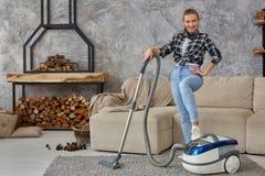 Młoda uśmiechnięta kobiety próżnia czyści dywan w żywym pokoju, nowożytny scandinavian wnętrze Dom, housekeeping obrazy stock