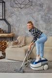 Młoda uśmiechnięta kobiety próżnia czyści dywan w żywym pokoju, nowożytny scandinavian wnętrze Dom, housekeeping zdjęcia stock
