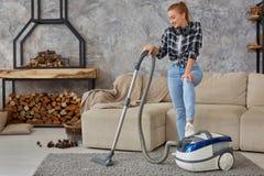 Młoda uśmiechnięta kobiety próżnia czyści dywan w żywym pokoju, nowożytny scandinavian wnętrze Dom, housekeeping zdjęcie royalty free