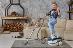 Młoda uśmiechnięta kobiety próżnia czyści dywan w żywym pokoju, nowożytny scandinavian wnętrze Dom, housekeeping fotografia royalty free