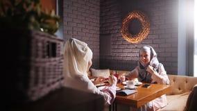 Młode muzułmańskie kobiety siedzi i opowiada w nowożytnej kawiarni zdjęcie wideo