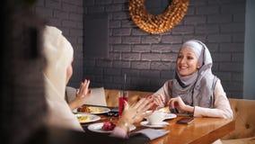 Młode muzułmańskie kobiety siedzi w kawiarni, opowiadać i śmiać się, zbiory wideo