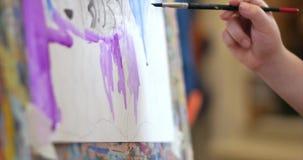 Młode ręki artysta, mały kobieta artysta malują kanwę z muśnięciem, siedzący remis na kanwie i stół proces zbiory wideo