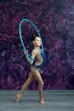 Młodej dziewczyny gimnastyczka w błękitnym kostiumu z rhinestones stoi na biurze fiołek ściana, trzyma obręcz za ona z powrotem zdjęcia royalty free