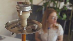 Młodej dziewczyny obsiadanie w cukiernianym dymieniu nargile, wolno exhaling gęstego bielu dym zbiory wideo