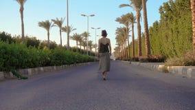 Młodej dziewczyny odprowadzenie na drodze z drzewkami palmowymi zbiory