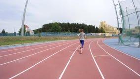 Młodej kobiety jogger biega przy miasto atletyki śladem podczas dnia szkolenia w zwolnionego tempa 4K wideo na UHD kamerze zbiory wideo