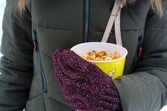 Młodej kobiety mienia popkorn w zimie, w mitynkach zdjęcia stock