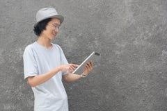 Młody atractive kreatywnie azjatykci mężczyzna wskazuje przy z fedora szkłami, kapeluszem i obrazy stock