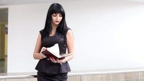Młody atrakcyjny kobiety odprowadzenie w biurze, czytelnicza informacja w notatniku zbiory wideo