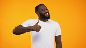 Młody brodaty czarny facet daje aprobatom, ono uśmiecha się przy kamerą na żółtym tle zbiory wideo