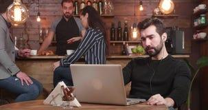 Młody brodaty mężczyzna patrzeje jego laptopu ekran podczas gdy pracujący daleko od coffe sklepu zdjęcie wideo
