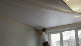Młody człowiek instaluje kanwę biały rozciągliwość sufit w pokoju mieszkanie zdjęcie wideo