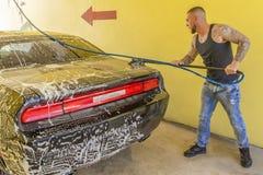 Młody człowiek mydli w górę jego czarnego samochodu fotografia stock