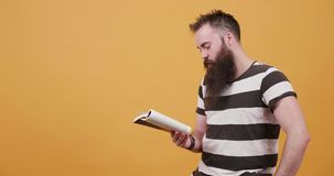 Młody człowiek po cichu czyta książkę i pieści jego wąsa i brodę zbiory wideo