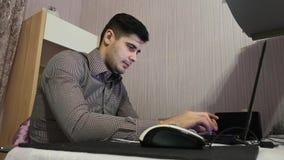 Młody człowiek pracuje na jego laptopie dostawać wszystkie jego biznes robi wcześnie rano zdjęcie wideo