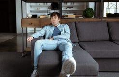 Młody człowiek relaksuje w domu w drelichowym gloth fotografia royalty free