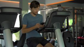 Młody człowiek trzyma telefon przed jego przy gym na ćwiczenie rowerze przygląda się w jego ręki Wszystkie uwaga jest wewnątrz zbiory