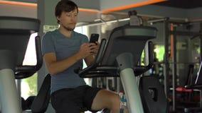 Młody człowiek trzyma telefon przed jego przy gym na ćwiczenie rowerze przygląda się w jego ręki Wszystkie uwaga jest wewnątrz zdjęcie wideo