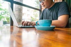 Młody człowiek używa laptop i pijący kawę obraz stock