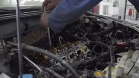 Młody człowiek wiruje z pomocą narzędzia silnik od auto mechanika naprawia samochód w rozkazie dla mnie zdjęcie wideo