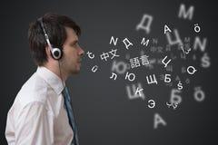 Młody człowiek z hełmofonami mówi w różnych językach obcych ilustracja wektor