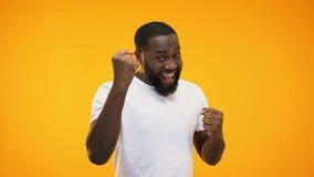 Młody czarny facet robi sukcesu gestowi z rękami, odosobnionymi na żółtym tle zbiory