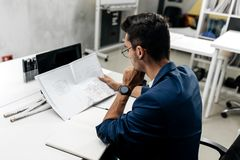 Młody elegancki ciemnowłosy architekt w szkłach w niebieskiej marynarce i pracuje z dokumentami na biurku w biurze obrazy royalty free