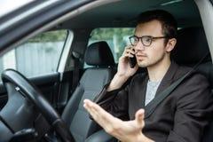 Młody facet opowiada na telefonie podczas gdy siedzący przy jego samochodem Bezpieczeństwo na drogach pojęcie obraz royalty free
