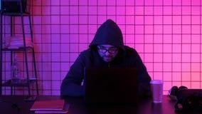 Młody męski pieniężny hacker przy biurowym siedzącym działaniem na laptopie zdjęcie royalty free