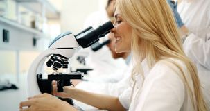 Młody naukowiec patrzeje przez mikroskopu w laboratorium fotografia royalty free