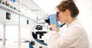 Młody naukowiec patrzeje przez mikroskopu w laboratorium fotografia stock