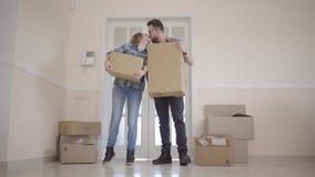 Młody pary chodzenie w nowego dom Para stoi na progu mienia pudełkach w ich rękach piękne zbiory wideo