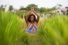 Młody pięknego i szczęśliwego czarnego afrykanina kobiety Amerykański obsiadanie przy rive pole outdoors ćwiczy joga medytację i  zdjęcie stock