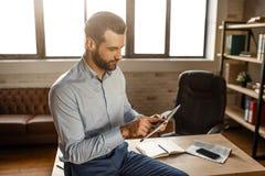 Młody przystojny biznesmen siedzi na stole i używa pastylkę w jego swój biurze Patrzeje skoncentrowanym Telefon dalej i notatniki obraz stock