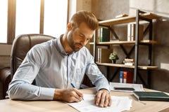 Młody przystojny biznesmena obsiadanie w jego swój biurze i pisać przy stołem Stawia podpis na dokumentach Worktime fotografia stock
