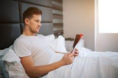 Młody przystojny mężczyzna czyta wewnątrz sypialnię skoncentrowany Światło dzienne Zakrywał z białą koc obraz stock
