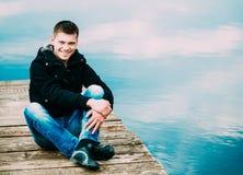 Młody Przystojny mężczyzna obsiadanie Na Drewnianym molu, Relaksujący, Myśleć Przypadkowy styl - cajgi, kurtka obrazy royalty free